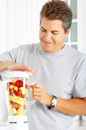 Happy man juicing with regular blender